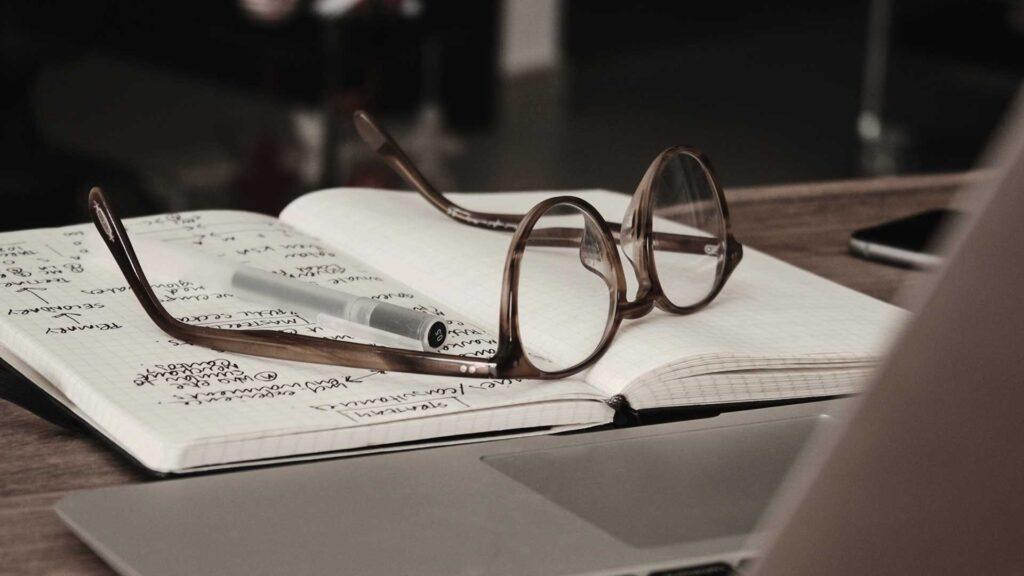 Brille und Notizbuch vor Computer