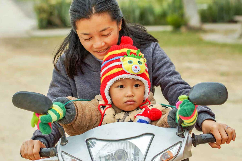 Laotische Mutter mit Kind auf Motorrad